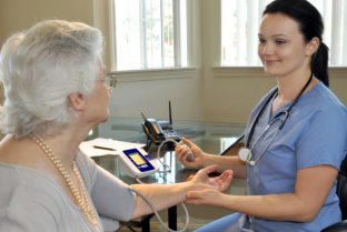 caregiver checking blood pressure of an elder